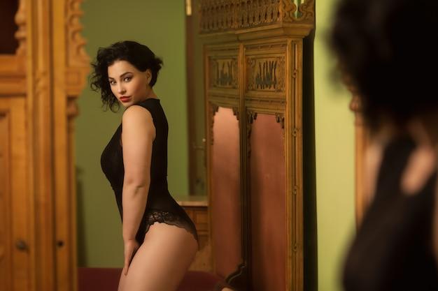 Piękna młoda kobieta w negligee siedzi na luksusowym łóżku Premium Zdjęcia