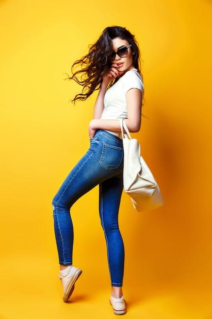 Piękna Młoda Kobieta W Okulary Przeciwsłoneczne, Biała Koszula, Niebieskie Dżinsy Pozowanie Z Torbą Premium Zdjęcia