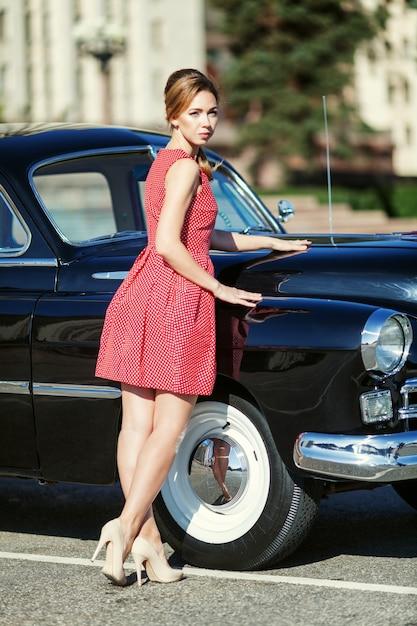 Piękna Młoda Kobieta W Rocznik Sukni Z Retro Samochodem Premium Zdjęcia