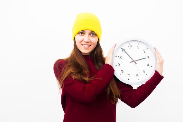 Piękna młoda kobieta w żółtym kapeluszu trzyma zegar w jej rękach uśmiechniętych i patrzejących ramę Premium Zdjęcia