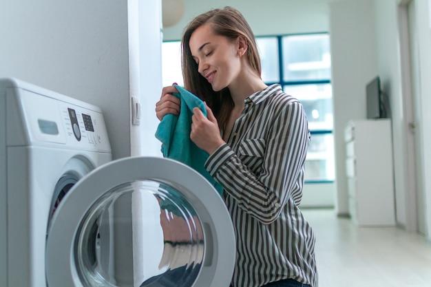 Piękna Młoda Kobieta Wącha Zapach świeżego Czystego Ręcznika Po Pralni W Domu I Cieszy Się Premium Zdjęcia