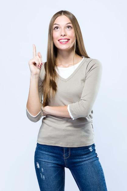 Piękna Młoda Kobieta Wskazuje Up Nad Białym Tłem. Darmowe Zdjęcia