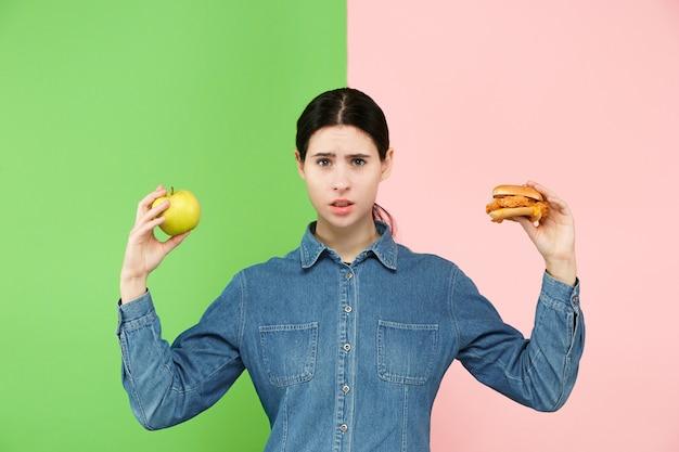 Piękna Młoda Kobieta Wybiera Między Owocami I Unhelathy Fast Food W Studio. Darmowe Zdjęcia