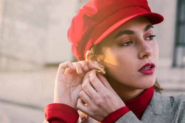 Piękna młoda kobieta z czerwoną nakrętką nad jej głową jest ubranym kolczyki w ucho Darmowe Zdjęcia