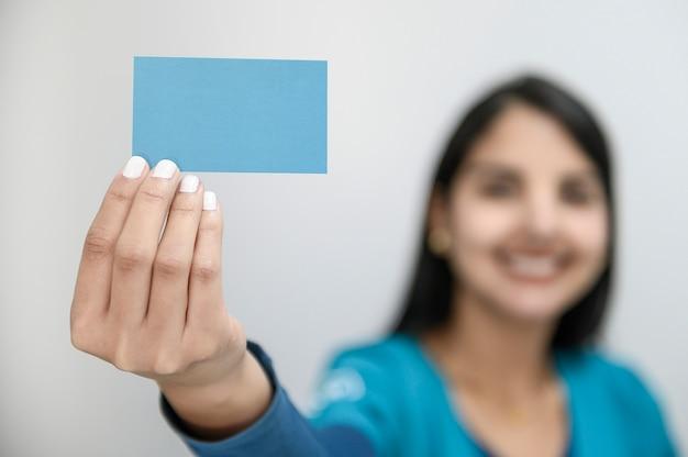 Piękna młoda kobieta z dużym uśmiechem wystawia pustą wizytówkę Premium Zdjęcia