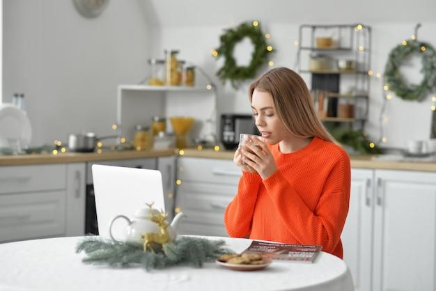 Piękna Młoda Kobieta Z Laptopa Picia Gorącej Czekolady W Domu W Wigilię Bożego Narodzenia Premium Zdjęcia