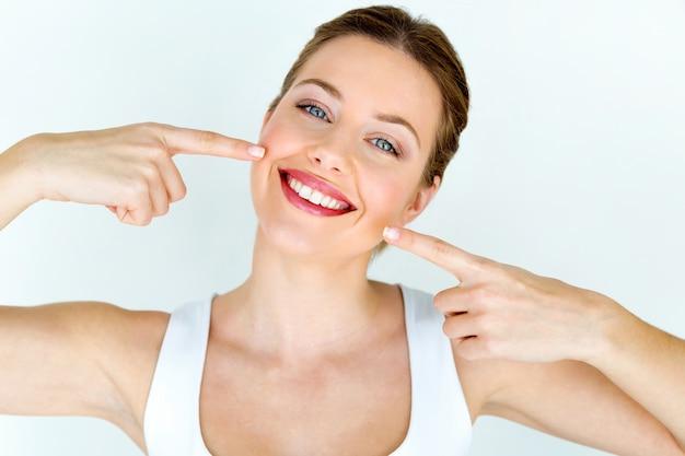 Piękna Młoda Kobieta Z Perfect Uśmiechem. Pojedynczo Na Białym. Premium Zdjęcia