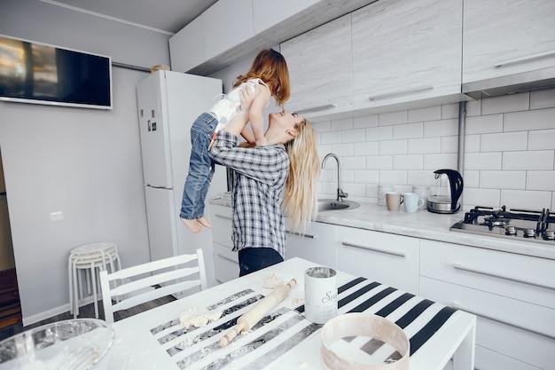 Piękna młoda matka z córeczką gotuje w kuchni w domu Darmowe Zdjęcia