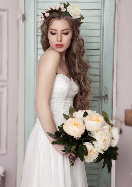 Piękna młoda panna młoda z kwiatami korony i romantyczną dekoracją różową i zieloną. drewniane pudełka butelki i różne dekoracje ślubne Premium Zdjęcia
