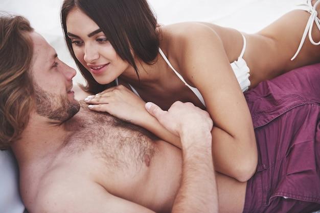 Piękna Młoda Para W Strojach Kąpielowych Na Plaży Przed Piaskiem Uśmiech I Przytulić. Darmowe Zdjęcia