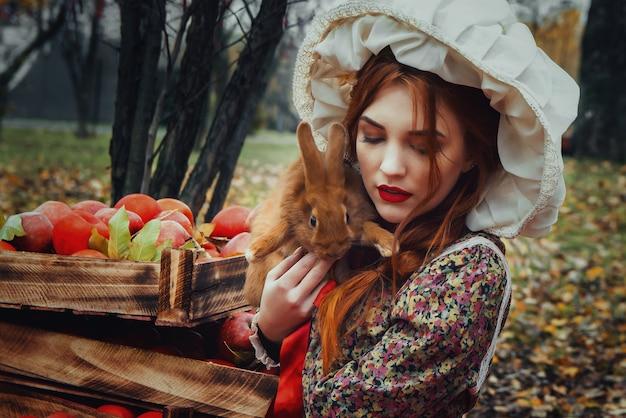 Piękna młoda seksowna dziewczyna z czerwonymi jabłkami w jesień ogródzie Premium Zdjęcia