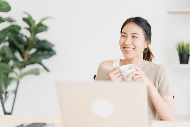 Piękna młoda uśmiechnięta azjatykcia kobieta pracuje na laptopie i pije kawę Darmowe Zdjęcia