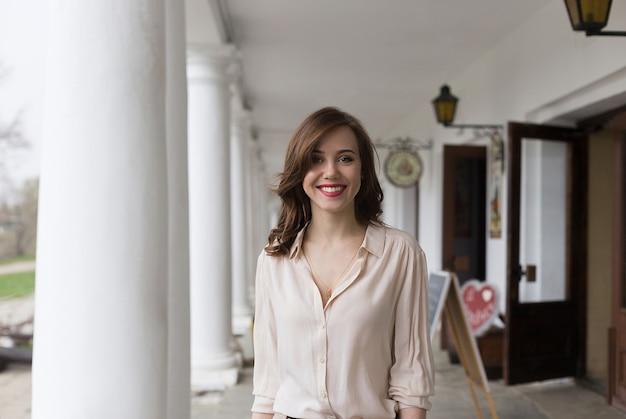Piękna młoda uśmiechnięta dziewczyna z uwodzicielską czerwoną pomadki pozycją na werandzie kawiarnia. kolumny i latarnie w tle Premium Zdjęcia