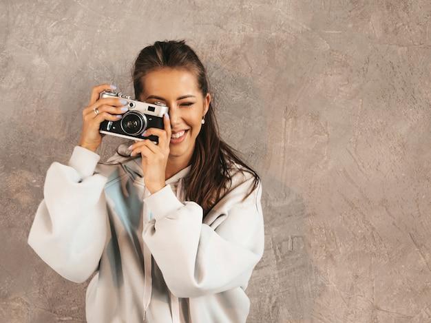 Piękna Młoda Uśmiechnięta Fotograf Dziewczyna Bierze Fotografie Używać Jej Retro Kamerę. Darmowe Zdjęcia