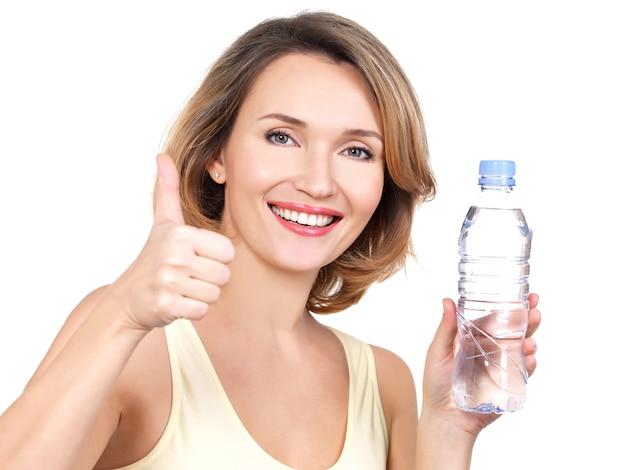 Piękna Młoda Uśmiechnięta Kobieta Z Butelką Wody Na Białym Tle. Darmowe Zdjęcia
