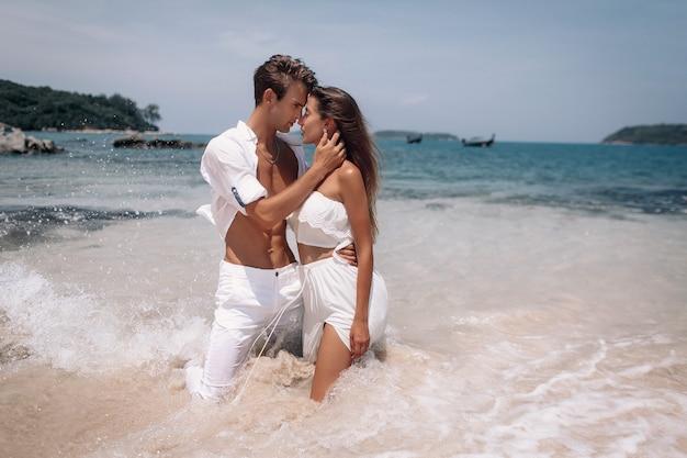 Piękna modelka pasja para całuje i obejmuje w wodzie morskiej. phuket. tajlandia Premium Zdjęcia