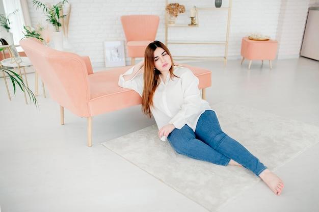 Piękna Modelka Plus Size Ubrana W Pustą Białą Koszulę Pozuje Na Tle Jasnego Pokoju Premium Zdjęcia