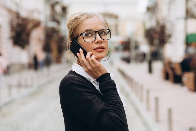 Piękna Modna Blond Biznesowa Kobieta W Szkłach Z Smartphone I Torebką Dokumenty W Jej Rękach Outdoors. Premium Zdjęcia