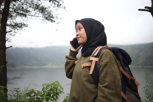 Piękna Muzułmańska Azjatka Rozmawia Przez Telefon W Pobliżu Dzikiego Górskiego Jeziora Premium Zdjęcia