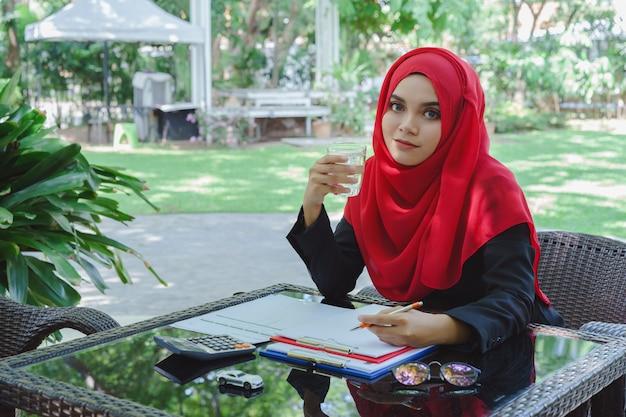 Piękna muzułmańska biznesowej kobiety czerwony hijab pracuje outdoors i pije wodę Premium Zdjęcia