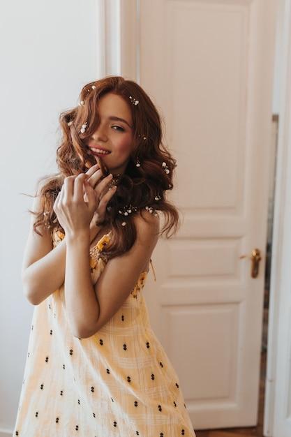 Piękna Pani W Stylowej żółtej Sukience Zalotnie Dotyka Włosów I Uśmiecha Się Słodko Do Białych Drzwi. Darmowe Zdjęcia