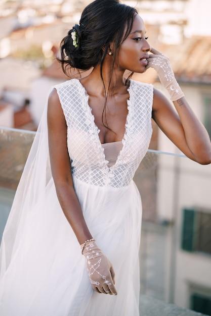 Piękna Panna Młoda African American W Białej Sukni ślubnej, Dotyka Jej Twarzy W Zabytkowych Rękawiczkach Premium Zdjęcia