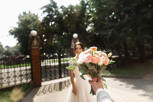 Piękna panna młoda w stylowej białej sukni, uśmiechając się spotyka pana młodego w parku Premium Zdjęcia