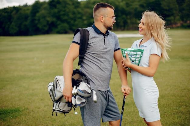 Piękna para bawić się golfa na polu golfowym Darmowe Zdjęcia