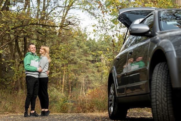Piękna para przytulanie za samochodem Darmowe Zdjęcia