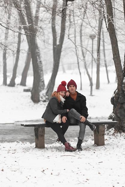 Piękna Para Siedzi Na ławce Długi Widok Darmowe Zdjęcia