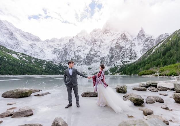 Piękna Para ślubna Stoi Na Lodzie Zamarzniętego Górskiego Jeziora Z Niesamowitą Zimową Górską Scenerią Darmowe Zdjęcia