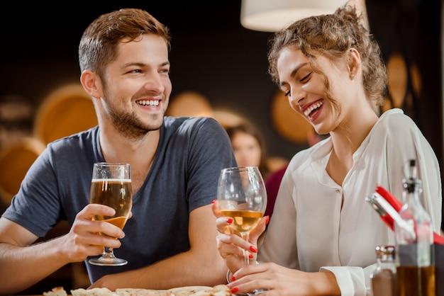Piękna para trzyma szkła biały wino i piwo w restauraci. Premium Zdjęcia