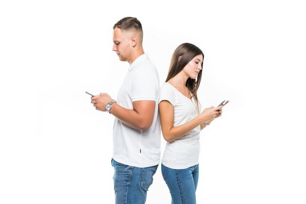 Piękna Para Z Telefonów Komórkowych, Pozostając Plecami Do Siebie Na Białym Tle Darmowe Zdjęcia