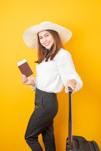 Piękna podróżnicza kobieta jest ekscytująca na żółtym tle Premium Zdjęcia