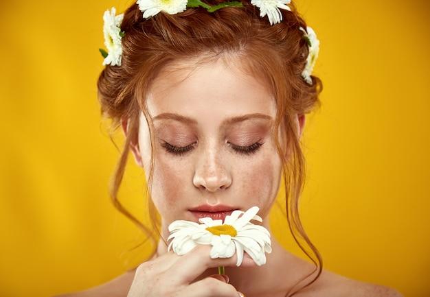 Piękna pozytywna rudowłosa dziewczyna z koroną rumianku na głowie Premium Zdjęcia