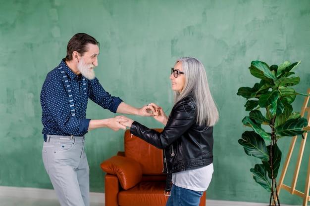 Piękna Radosna Stylowa Starsza Kobieta O Długich Prostych Siwych Włosach, Tańcząca Wraz Ze Swoim Przystojnym Brodatym Mężem Premium Zdjęcia