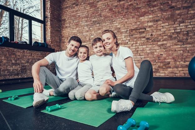 Piękna rodzina w białych koszulkach siedzi w dużej siłowni. Premium Zdjęcia