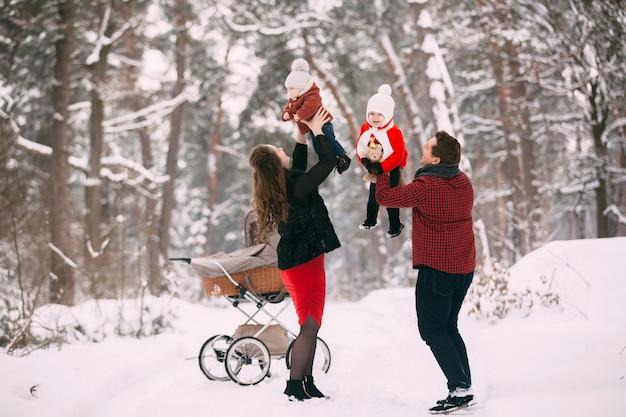 Piękna Rodzina Z Wózkiem Retro Idzie Przez Zimowy śnieżny Las. Matka, Ojciec, Córka I Synka Korzystających Dzień Na świeżym Powietrzu. święta, święta, Szczęście Razem, Zakochane Dzieciństwo. Premium Zdjęcia