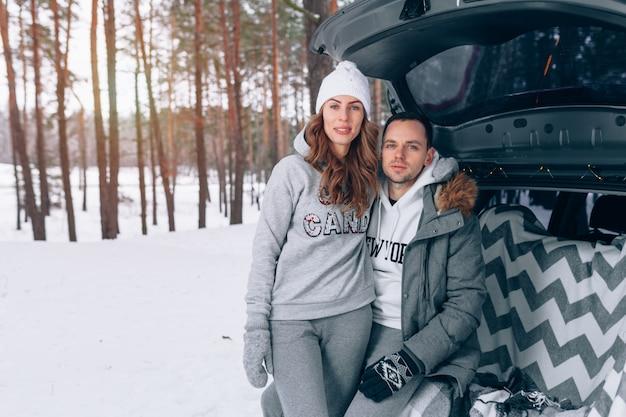 Piękna Rodzinna Para W śnieżnym Zima Lesie Siedzi W Bagażniku Twój Samochód Premium Zdjęcia