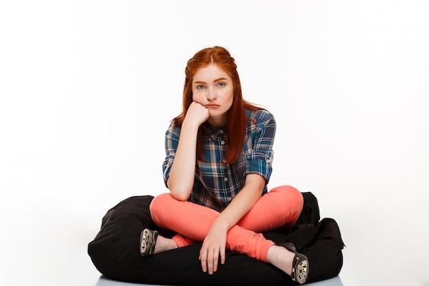 Piękna Ruda Dziewczyna Siedzi Ze Skrzyżowanymi Nogami Na Białej ścianie. Darmowe Zdjęcia