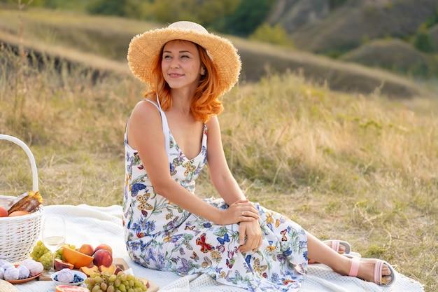 Piękna Rudowłosa Dziewczyna Cieszy Się Zachodem Słońca Na Naturze. Piknik W Terenie. Premium Zdjęcia
