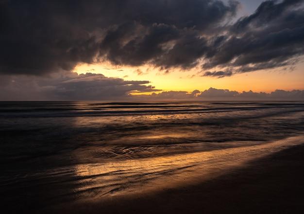 Piękna Sceneria Falującego Morza Pod Zachmurzonym Niebem O Wschodzie Słońca Darmowe Zdjęcia