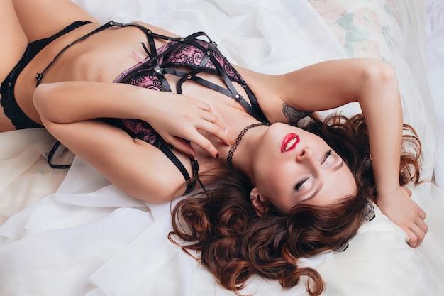 Piękna Seksowna Naga Dziewczyna W Bieliźnie Z Paskiem Na Białym łóżku. Erotyczne Sesje Zdjęciowe Urocze Atrakcyjne Kobiety Premium Zdjęcia