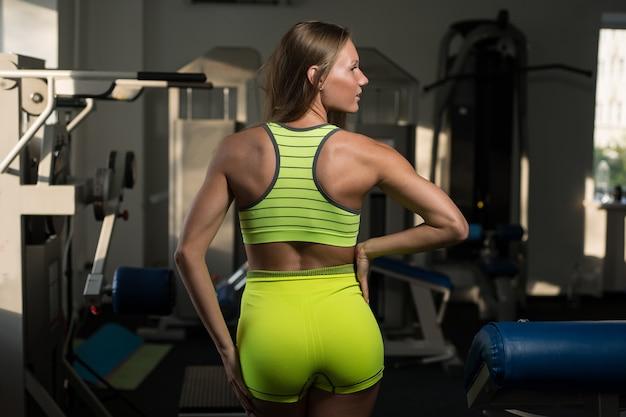 Piękna seksowna sportowa mięśniowa młoda dziewczyna. dziewczyna pozuje po treningu. Premium Zdjęcia