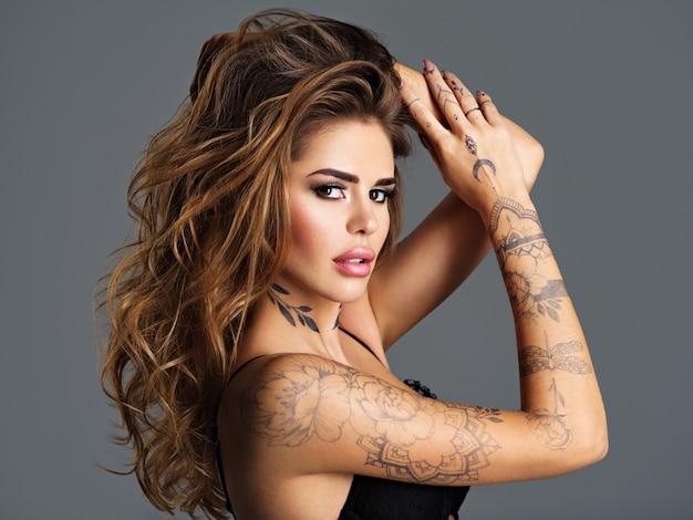 Piękna Sexy Dziewczyna Z Tatuażem Na Ciele. Portret Młodej Dorosłej Atrakcyjnej Kobiety Z Brązowymi Włosami. Darmowe Zdjęcia