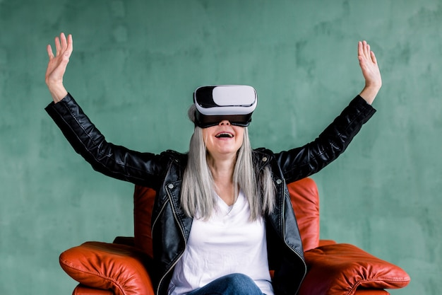Piękna Siwowłosa Starsza Kobieta Ubrana W Czarną Skórzaną Kurtkę, Siedząca W Wygodnym Czerwonym Fotelu W Okularach Rzeczywistości Wirtualnej, Dotykająca Powietrza Rękami Premium Zdjęcia