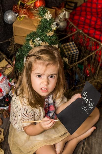Piękna śliczna Mała Dziewczynka Pisze List Do świętego Mikołaja W Pobliżu świątecznych Dekoracji Na Drewnianej Podłodze Darmowe Zdjęcia