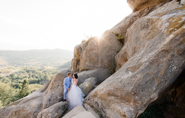 Piękna ślub Para W Słoneczny Dzień Stoi Na Ogromnych Skałach Z Malowniczym Widokiem Na Las Darmowe Zdjęcia