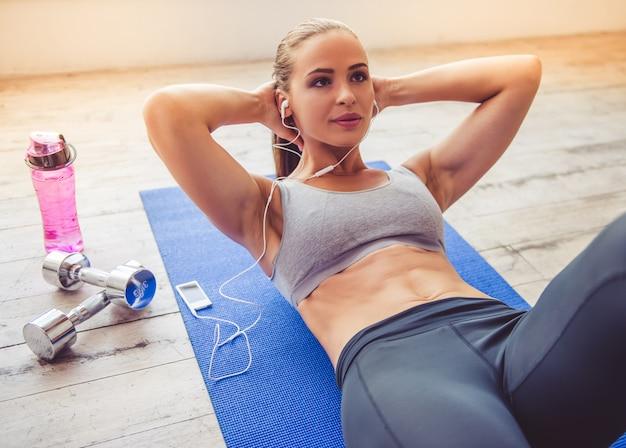 Piękna sportowa dama w słuchawkach słucha muzyki. Premium Zdjęcia