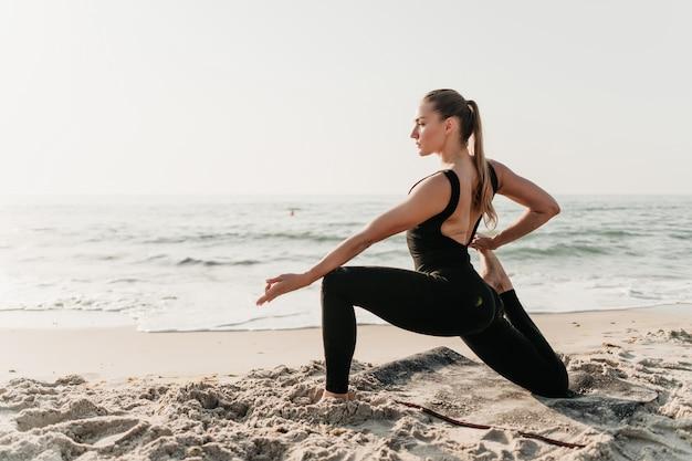 Piękna Sporty Kobieta Robi Joga Asana Na Plażowym Pobliskim Oceanie Premium Zdjęcia